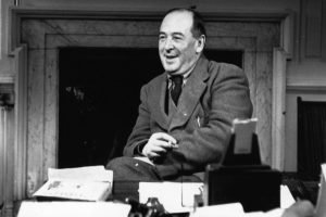 CS Lewis, who carried on a Latin correspondence, sitting at a desk smiling